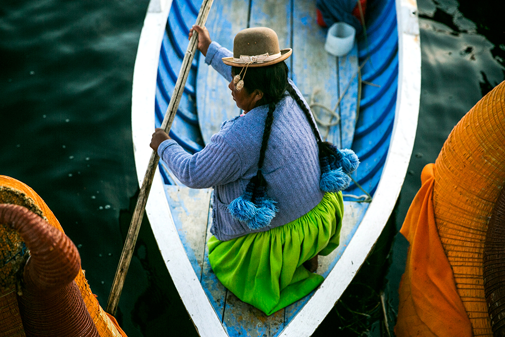 One of the villagers guides our boat as we depart a floating village on Lake Titicaca in Peru.