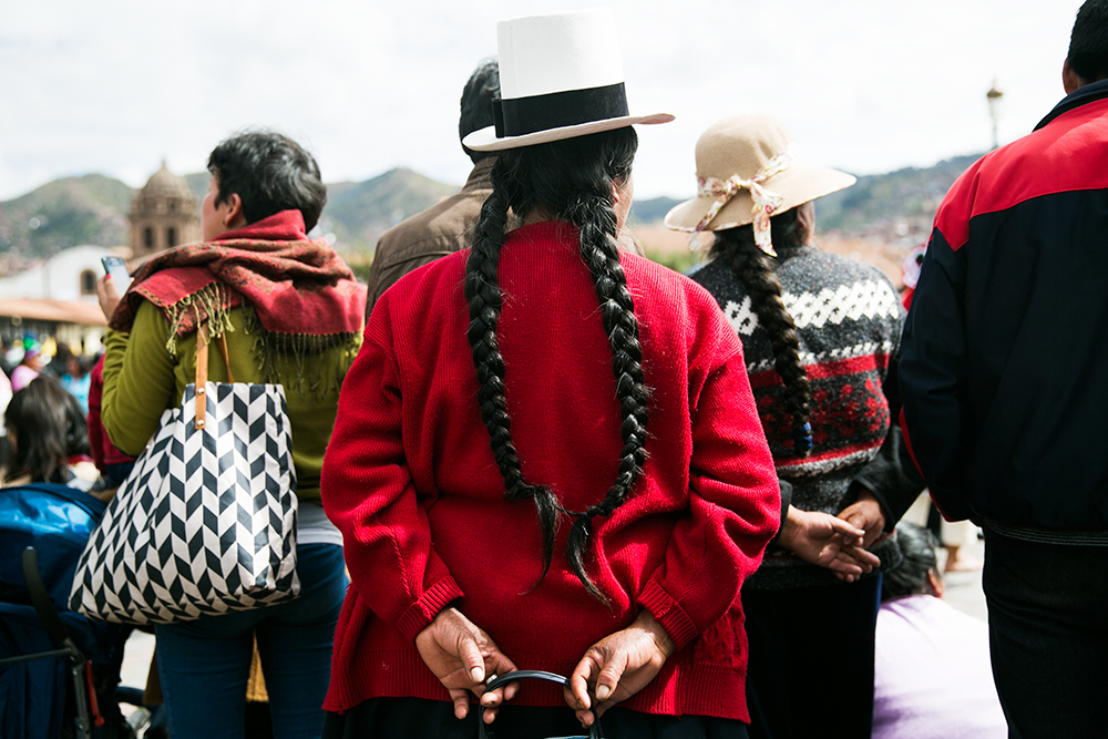 A woman watches during the celebration of Cruz Velacuy in Cusco, Peru.