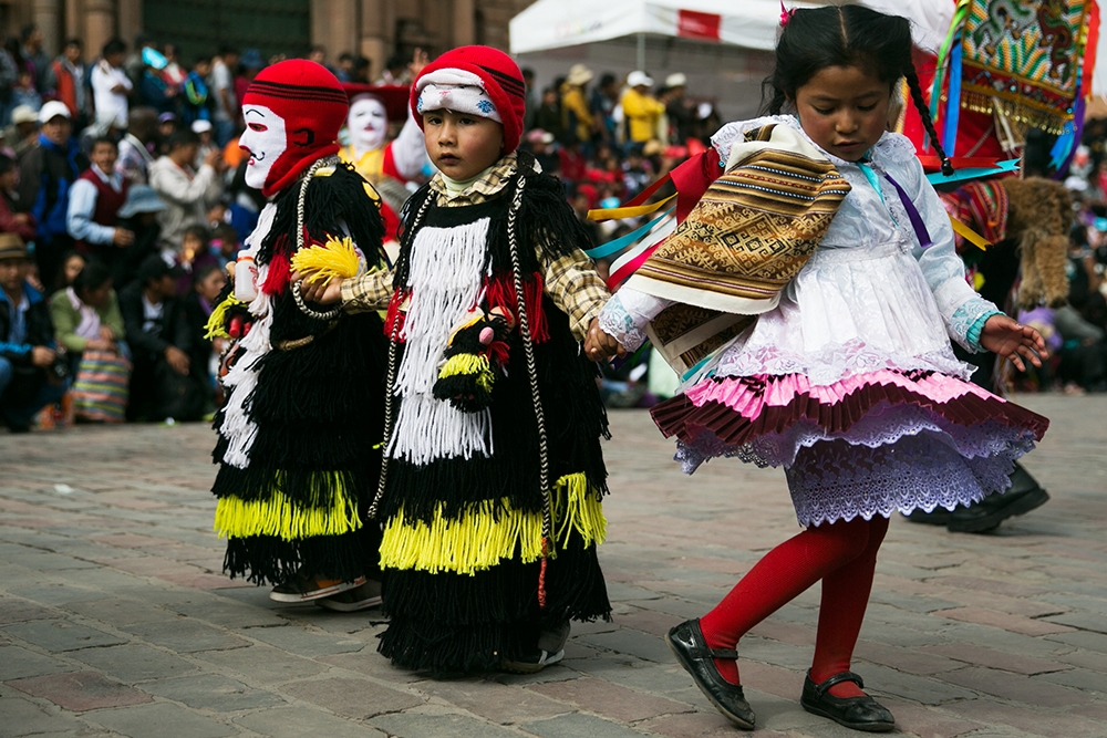 A young girl dances her way through the street during the celebration of Cruz Velacuy in Cusco, Peru.