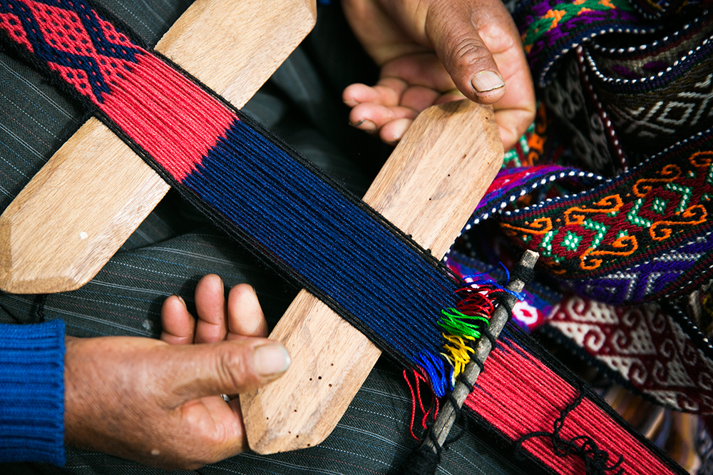 A woman weaves belts while trying to sell us on buying one in Cusco, Peru.