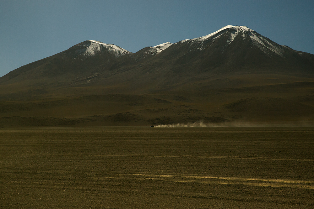 A distant 4x4 races across the desert on our way to Uyuni, Bolivia.