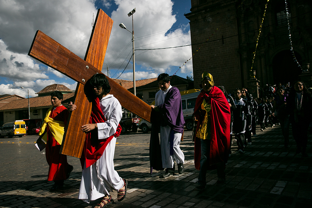 A student dressed as Jesus carries a cross through the streets of Cusco, Peru.