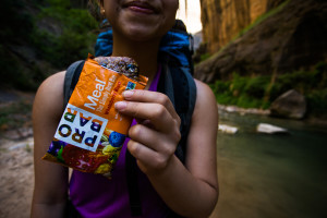 A traveler eats a Probar Meal while backpacking in Zion National Park.