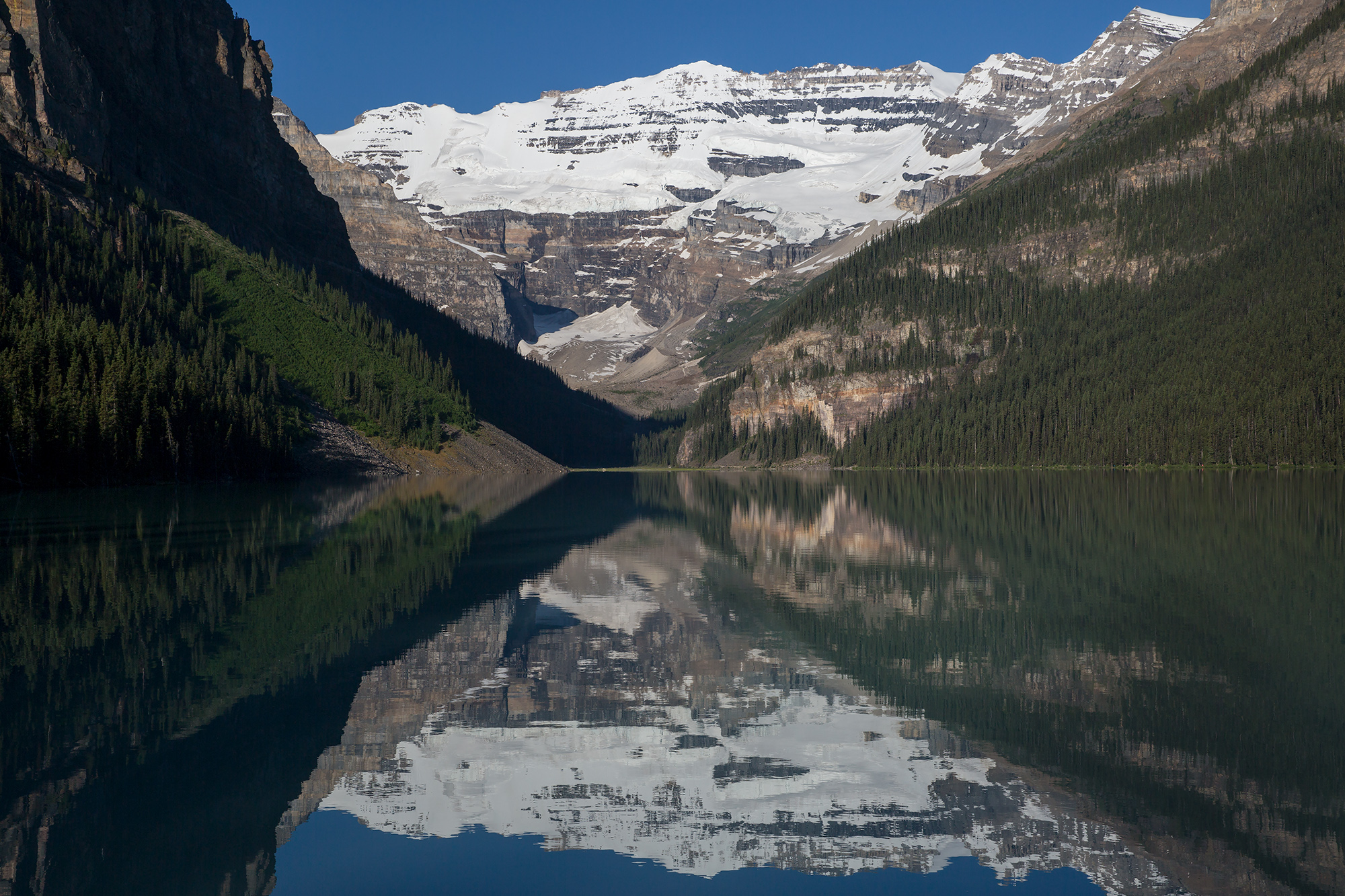 The still waters of Lake Louise shortly after sunrise in Banff National Park, Canada.