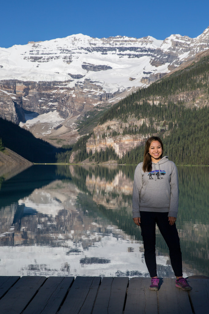 Britnee stands for a photo in the morning light on the shore of Lake Louise shortly after sunrise in Banff National Park.