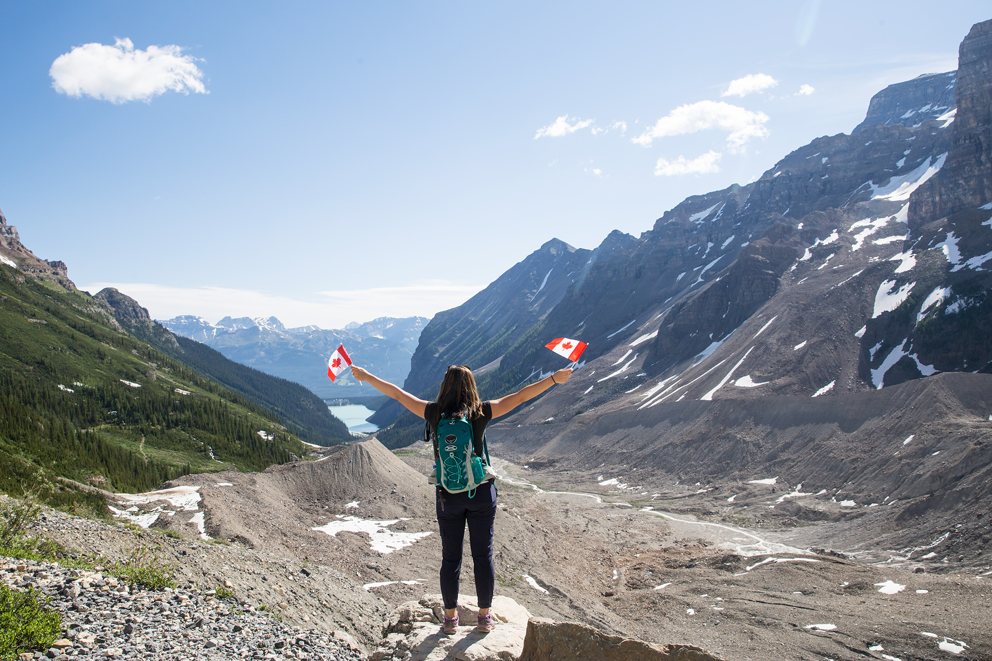 Britnee waves Canadian flags while hiking to the viewpoint at the end of the Plain of the Six Glaciers.