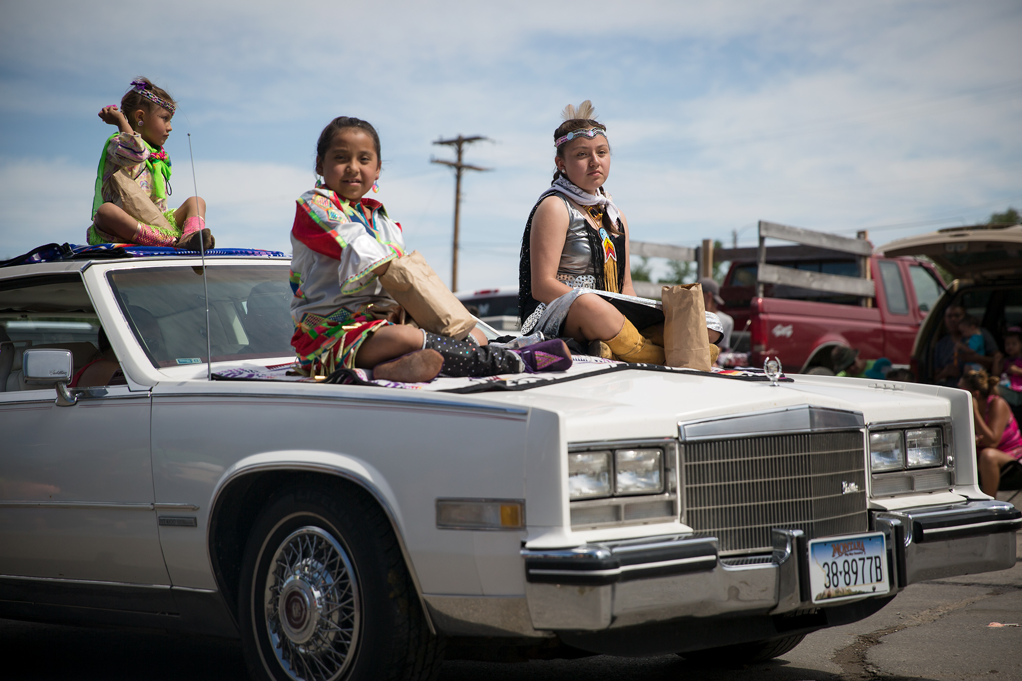 Young children sit on a car during a parade through Browning, Montana during North American Indian Days.