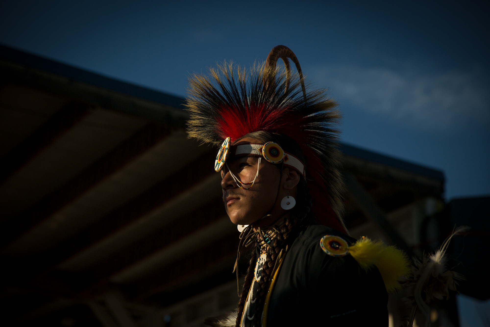 A dancer is bathed in evening light as he prepares to enter the ring during during the pow wow at North American Indian Days in Browning, Montana.