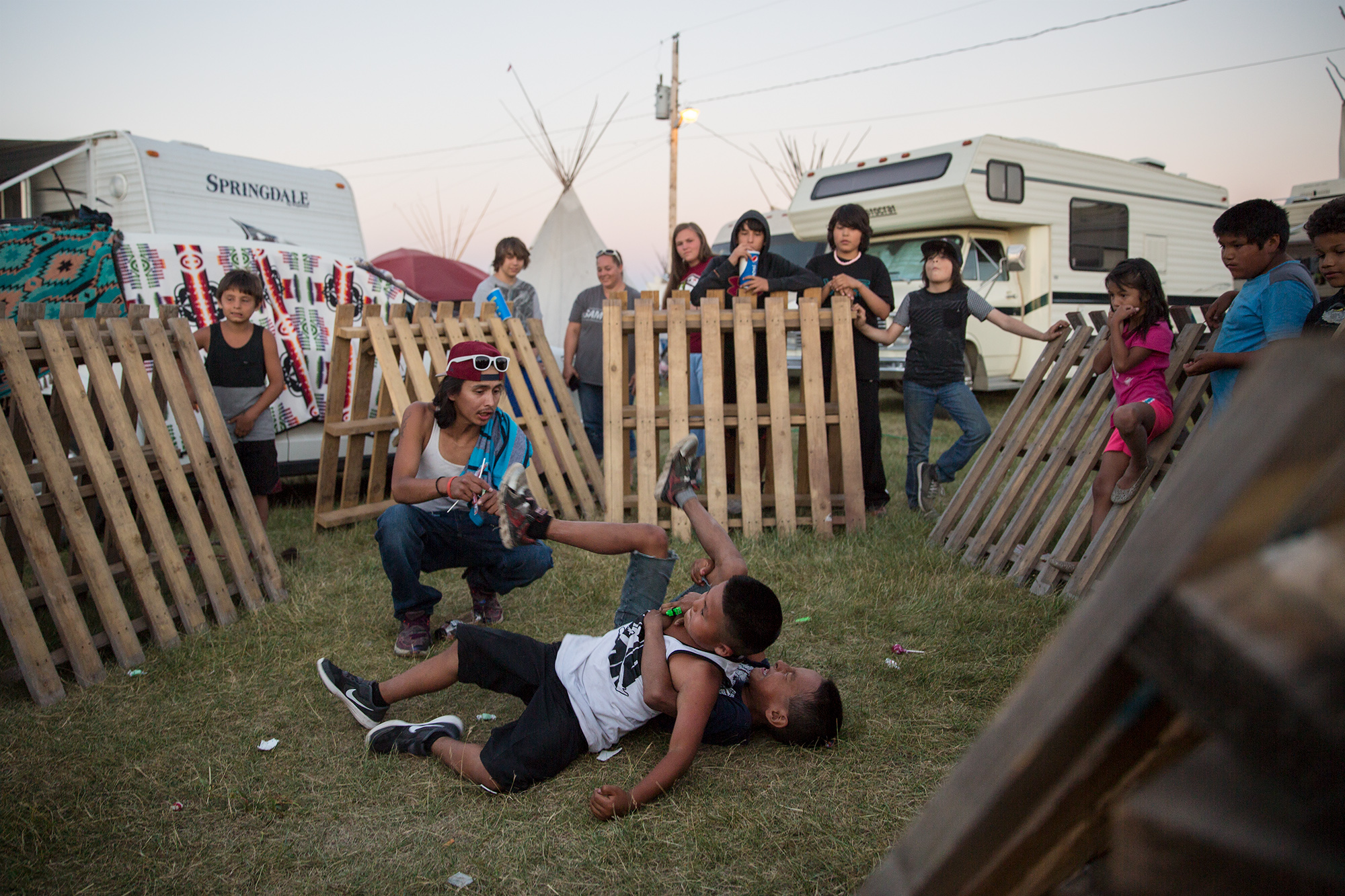 Young kids entertain themselves by wrestling outside the pow wow at North American Indian Days in Browning, Montana.